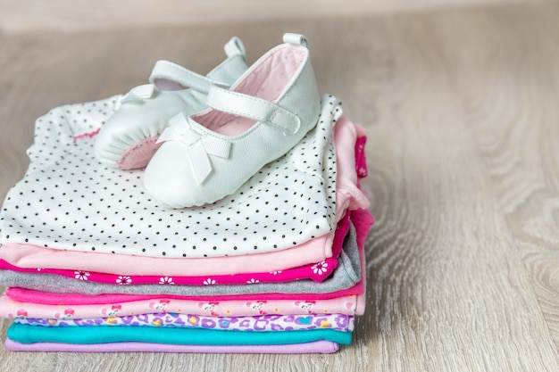 Gefalteter rosa und weißer body mit schuhen darauf auf grauem hölzernem hintergrund. windel für neugeborene. stapel babykleidung. kinderoutfit. speicherplatz kopieren.
