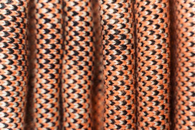 Gefalteter synthetischer strickstoff mit musterelementen aus roten, schwarzen und weißen garnen in nahaufnahme. mehrfarbig gemusterte strickstruktur. hintergrund