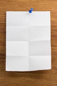 Gefaltetes briefpapier auf hölzernem hintergrund
