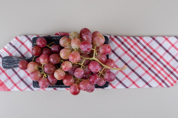 Gefaltetes handtuch unter einem kleinen tablett mit roten trauben auf marmor
