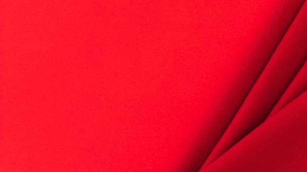 Gefaltetes rotes textilgewebe auf farbigem hintergrund