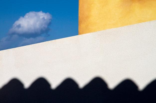 Gefangene wolke. zwei außenwände des hauses, weiß und gelb, banden ein kleines stück blauen himmels, wo eine kleine wolke fliegt