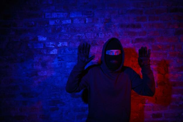 Gefangener einbrecher, der nachts in der nähe einer mauer steht