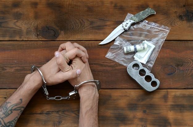 Gefesselte hände eines tätowierten kriminellen verdächtigen und ein beweispaket aus plastik mit reißverschluss zur untersuchung