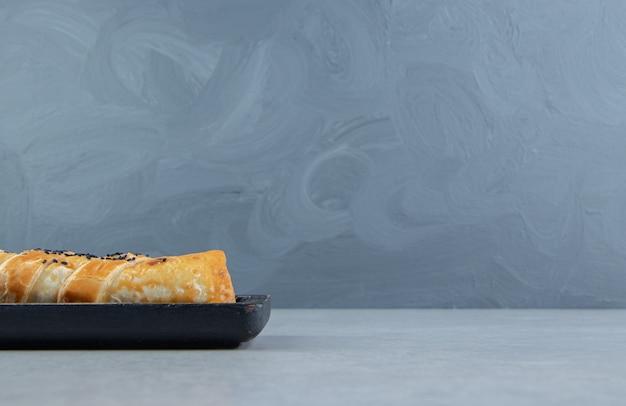 Geflochtenes brötchen gefüllt mit fleisch auf schwarzem teller.