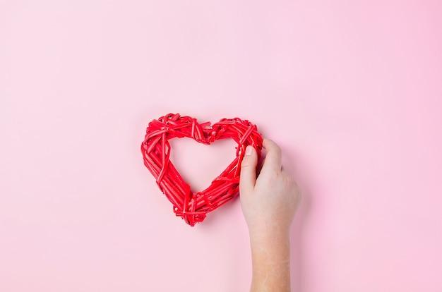 Geflochtenes rotes weidenherz der zweige in den händen eines mädchens auf rosa hintergrund.