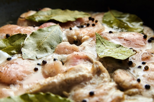 Geflügelfleisch kochen. stücke rohes hähnchenfilet mit lorbeerblättern und pfeffer