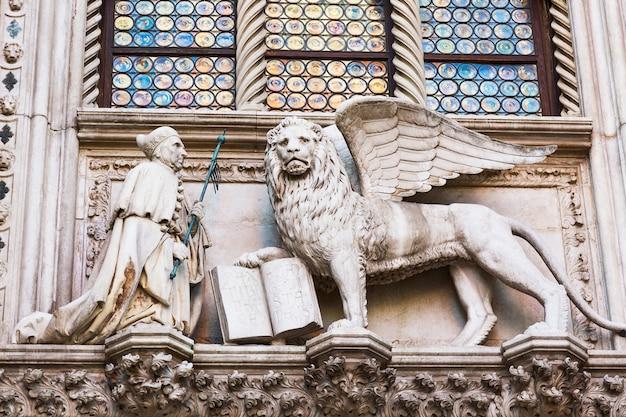 Geflügelter löwe und ein priester, detail des dogenpalastes palazzo ducale in venedig, italien,