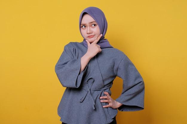 Geflüstertes porträt einer glücklichen jungen asiatischen frau mit hijab, die auf gelbem hintergrund zeigt