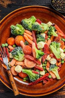 Gefroren geschnittenes gemüse, brokkoli, paprika, tomaten, karotten, erbsen und mais auf einem teller. dunkler holztisch. draufsicht.