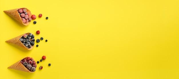 Gefrorene beeren - erdbeere, blaubeere, brombeere, himbeere in den waffelkegeln auf gelb