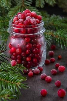 Gefrorene cranberry-beere in einem glas auf dem tisch mit zweigen des weihnachtsbaumes verziert. weihnachten winterzeit