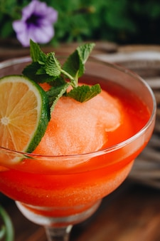 Gefrorene erdbeer-margarita-cocktail-nahaufnahme neben blumen