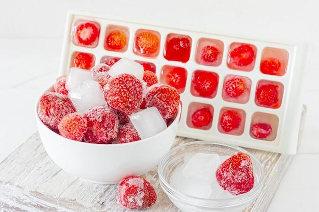 Gefrorene erdbeere mit eiskristallen auf rosa hintergrund.