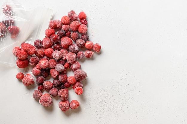 Gefrorene erdbeeren in plastikverpackung auf weißer ansicht von oben