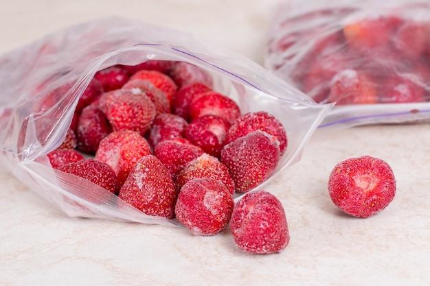 Gefrorene erdbeeren in säcken, nahaufnahme. vorräte an mahlzeiten für den winter.