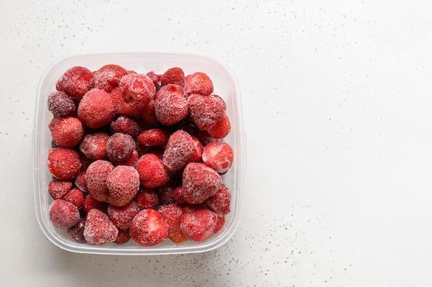Gefrorene erdbeeren und kirschen im behälter auf weißem hintergrundkopierraum