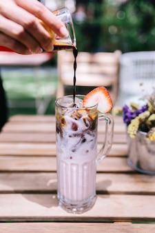 Gefrorene erdbeermilch, die mit espresso gießt.