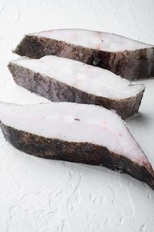 Gefrorene filets von weißem fisch, seelachs-set, auf weißem steintischhintergrund