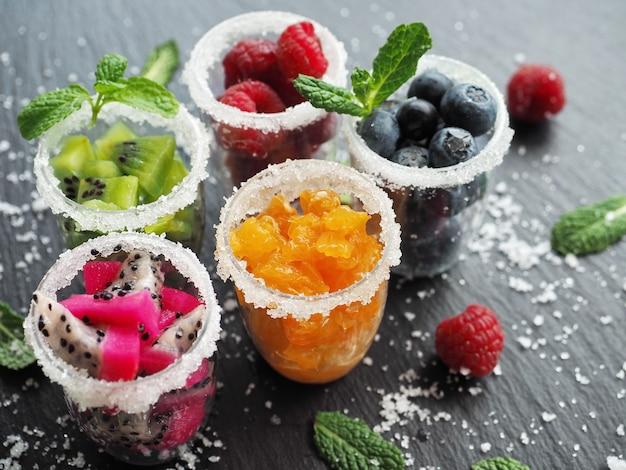 Gefrorene früchte und beeren in gläsern auf dunkler oberfläche