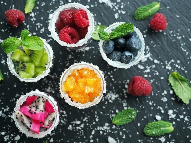 Gefrorene früchte und beeren mit zucker und minzblättern in gläsern