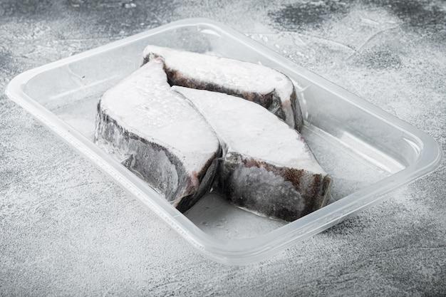 Gefrorene grönland-heilbutt-steaks vakuumverpackungsset auf grauem steintisch