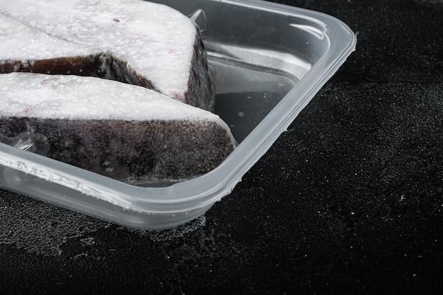 Gefrorene grönland-heilbutt-steaks vakuumverpackungsset, auf schwarzem, dunklem steintisch