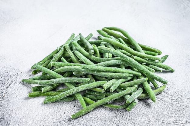 Gefrorene grüne bohnen auf dem weißen küchentisch.