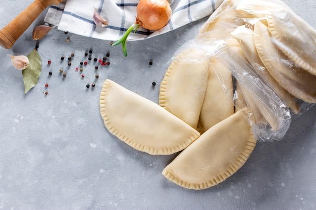 Gefrorene halbfabrikate in der tasche auf grauem tisch. russische knödel. fleischklößchen, ravioli. knödel mit füllung. platz kopieren