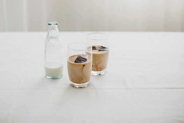 Gefrorene kaffee-eiswürfel in einem mit milch übergossenen glas, um ein erfrischendes sommer-eiskaffee-getränk zuzubereiten. weißer hintergrund, isoliert, kopienraum.