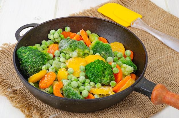 Gefrorene karotten, brokkoli und grüne erbsen in der pfanne