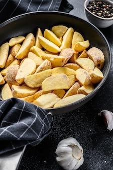 Gefrorene kartoffelschnitze in einer pfanne. pommes frittes. schwarzer hintergrund. draufsicht