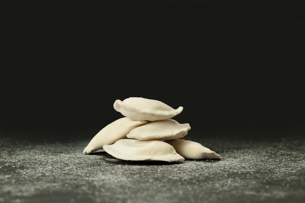 Gefrorene knödel auf einer dunklen oberfläche, mit mehl bestreut