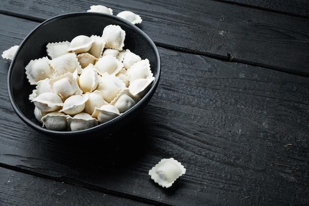 Gefrorene knödel tortellini und ravioli in schwarzer schüssel, auf schwarzem holztischhintergrund, mit kopienraum und platz für text