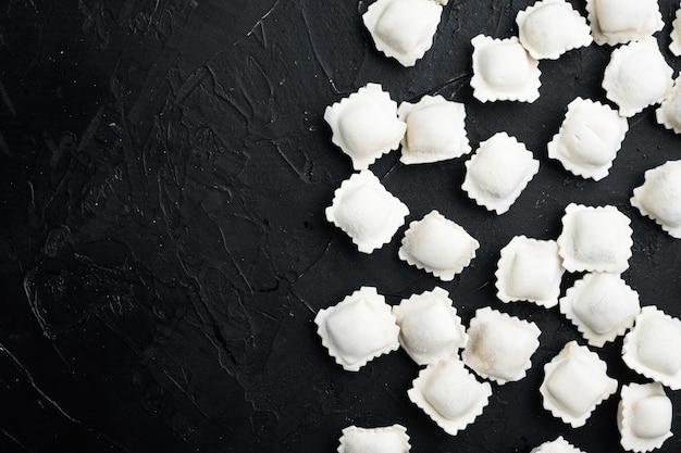 Gefrorene knödel tortellini und ravioli set, auf schwarzem hintergrund, draufsicht flach, mit kopienraum und platz für text