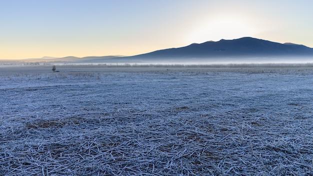Gefrorene landschaft mit eis auf dem boden und gebirgshintergrund am horizont mit der aufgehenden sonne. spanien.