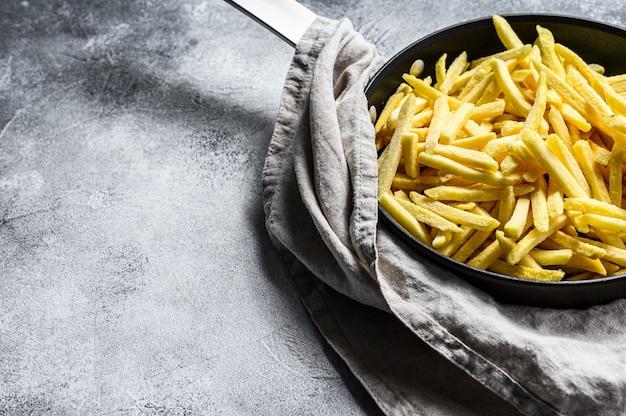 Gefrorene pommes frites in einer pfanne. grauer hintergrund. draufsicht. platz für text