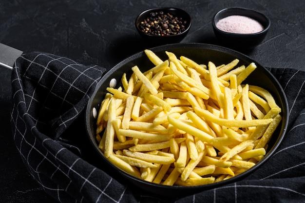 Gefrorene pommes frites in einer pfanne. schwarzer hintergrund. draufsicht