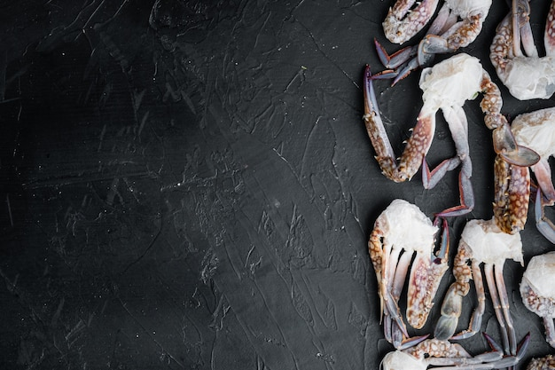 Gefrorene rohe blaue schwimmkrabben teile gesetzt, auf schwarzem tisch, draufsicht flach legen