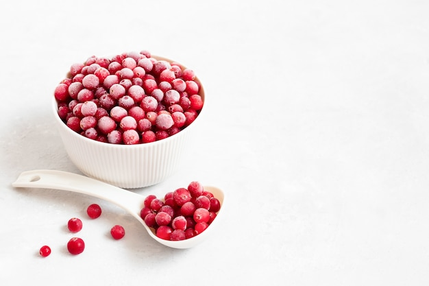 Gefrorene rote beeren in einer schüssel mit einem löffel auf einem weißen hintergrund. preiselbeeren mit frost. vegetarisches essen. platz für text.