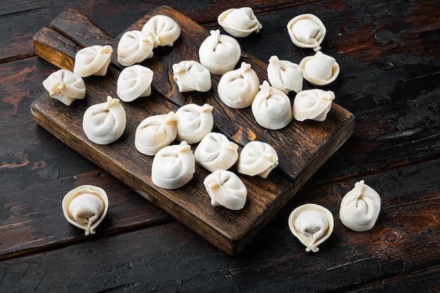 Gefrorene tortellini auf schneidebrett auf altem dunklem holztischhintergrund