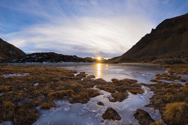 Gefrorener alpiner see der großen höhe, reflexionen bei sonnenuntergang