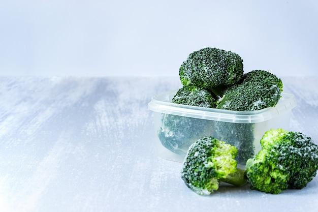 Gefrorener brokkoli in einer plastikbox auf grauem tisch, kopienraum