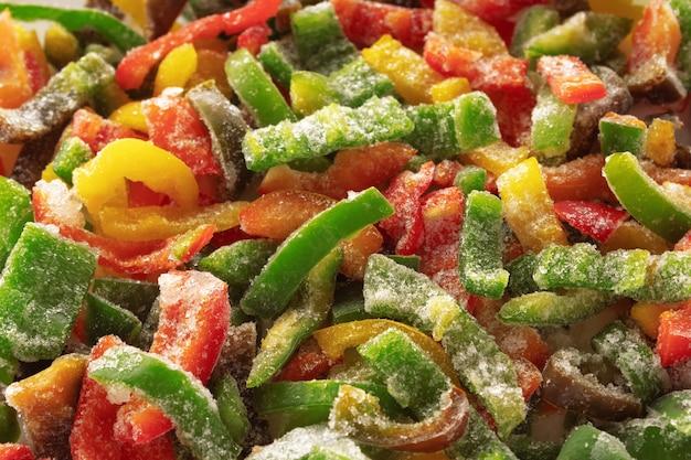 Gefrorener geschnittener paprika mit eis bedeckt. gefrorenes gemüse hintergrund. selektiver fokus.