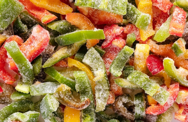 Gefrorener geschnittener paprika mit eis bedeckt. gefrorenes gemüse hintergrund.