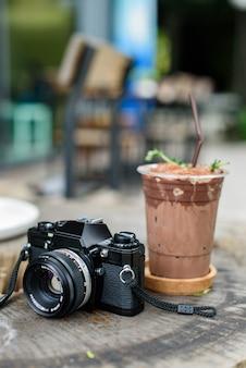 Gefrorener kakao mit filmkamera auf dem holztisch Premium Fotos