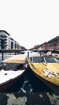 Gefrorener kanal mit gebäuden und booten in kopenhagen