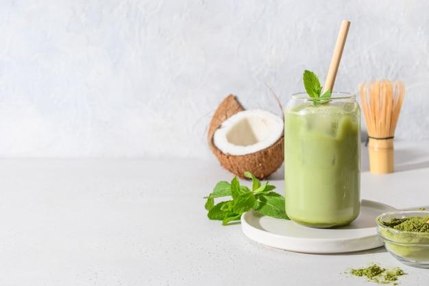 Gefrorener latte grüner matcha-tee mit kokosmilchgarniturminze auf weißem hintergrund.