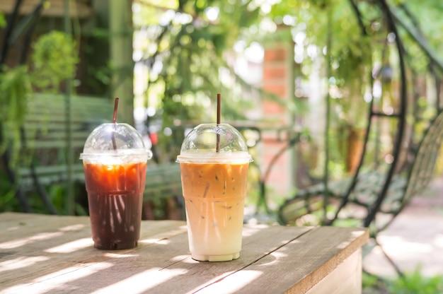 Gefrorener latte- und americanokaffee auf einem holztisch.