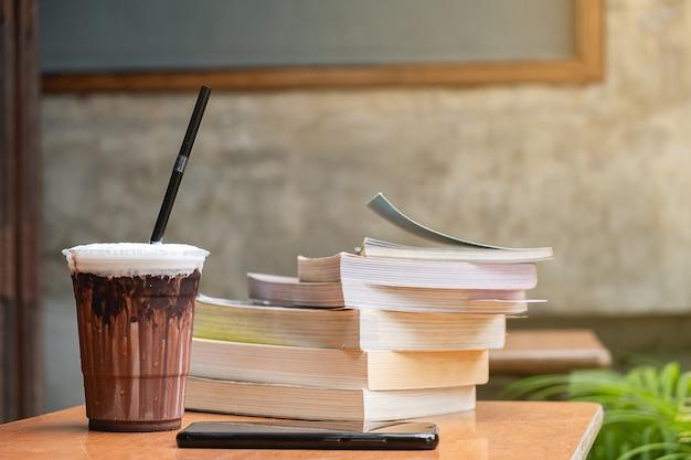 Gefrorener latte und buch auf schreibtisch-, bildungs- und geschäftskonzept, kopienraum